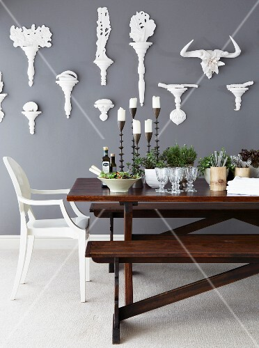 Candles, pots of herbs, crockery and salad on table in front of grey wall with white, decorative brackets