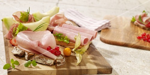 Slices of bread with cold meats and melon wedges