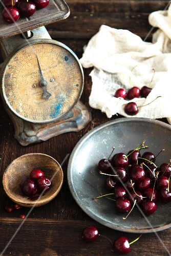 A still life featuring cherries and antique kitchen scales