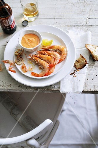 Garlic prawns with dip, chunks of bread, and beer on a table