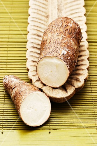 Cassava root, sliced in two, in a wooden dish