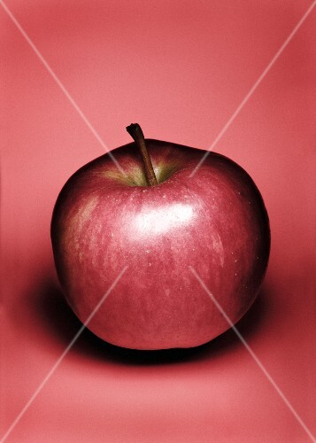 A red apple against a red background
