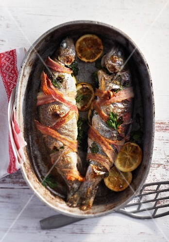 Trout wrapped in bacon in a roasting tin