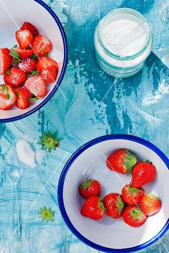 Fresh strawberries in the bowls with sugar