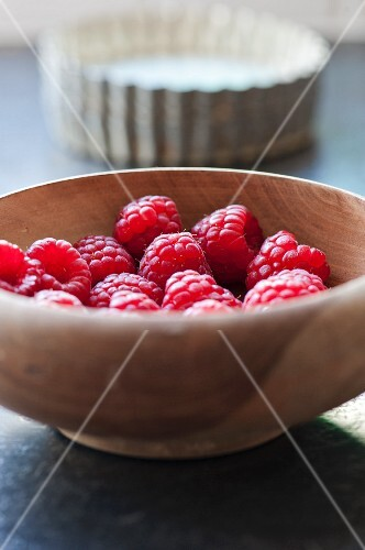 raspberries in a bowl with tart baking tins
