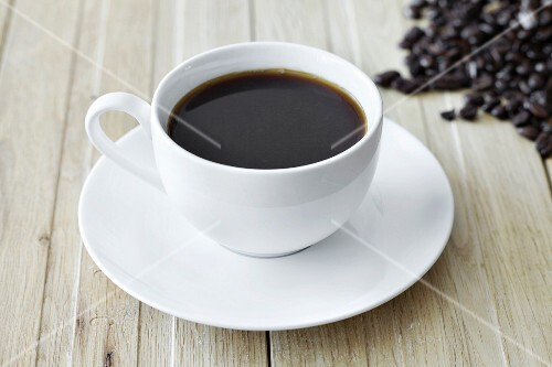 Black coffee in a white cup and coffee beans