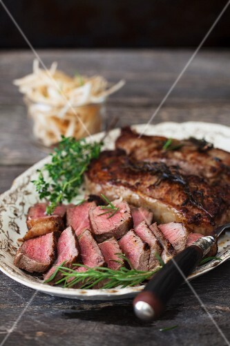 Whole and Sliced New York Strip Steaks on a Platter with Rosemary