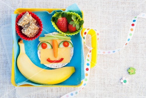 A healthy snack including a face made out of fruit and vegetables
