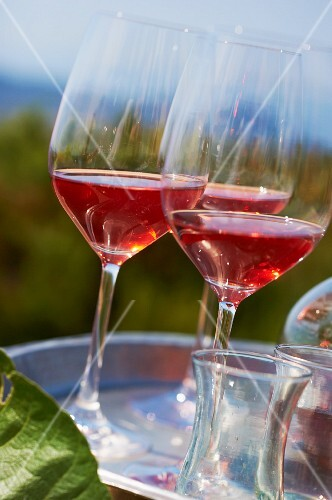 Three glasses of rosé wine on a tray outdoors (Domaine de la Begude, southern France)