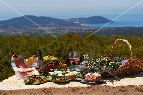 A table laid with bread, cheese, grapes and wine in the Domaine de la Begude region in southern France