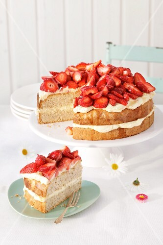 Strawberry layer cake with vanilla buttercream, partly sliced