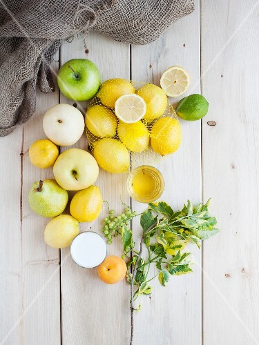A still life featuring yellow and green fruits (view from above)