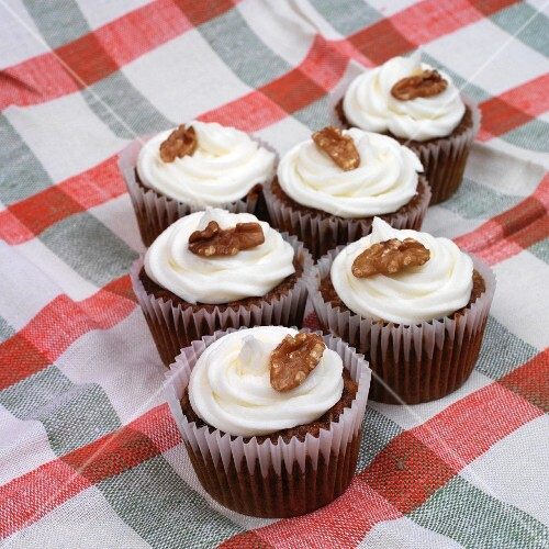 Cupcakes topped with icing and walnuts