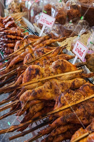 A market stall selling gai yang (grilled chicken skewers, Thailand)