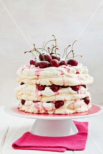 Pavlova with meringue, whipped cream, cherries, cherry sauce and icing sugar, on a cake stand