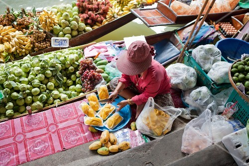 A woman selling fruit from a boat at the market (Bangkok, Thailand)