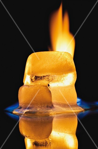 A burning ice-cube against a black background