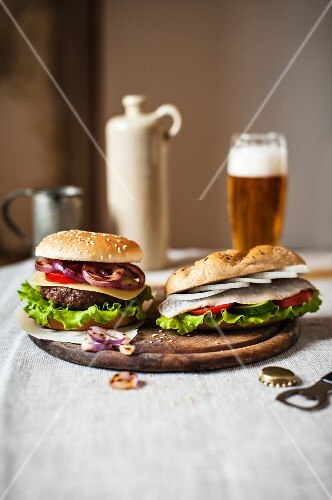 A beefburger and a herring sandwich on a wooden board