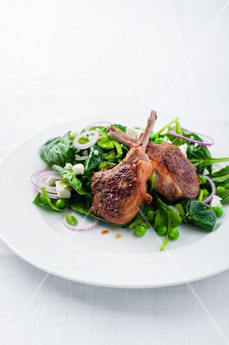 Lamb chops on a spinach salad with peas, onions and feta