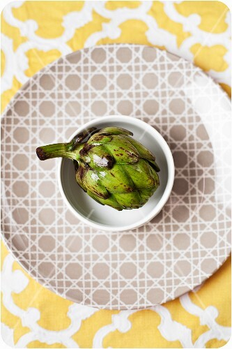 Baby Artichoke in a White Bowl on a Patterned Plate