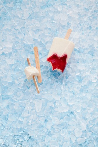 Milk ice lollies with raspberry sauce on crushed ice, partly eaten