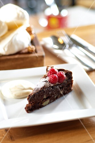 A slice of chocolate and almond torte with raspberries