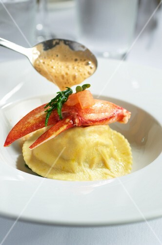 Lobster ravioli being drizzled with sauce