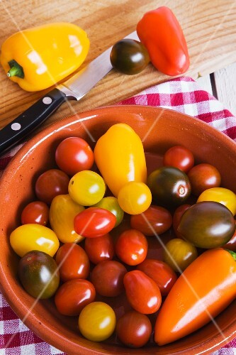 Cherry tomatoes and peppers in a bowl and on a chopping board