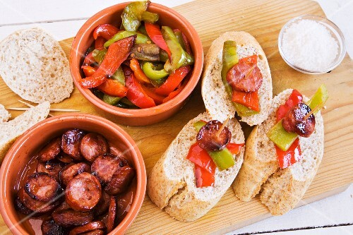 Peppers with chorizo and bread on a wooden board (Spain)