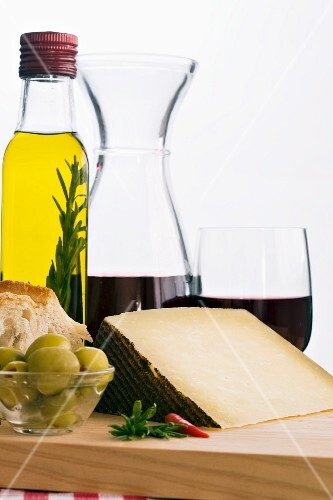 A still life featuring olive oil, red wine, bread, olives and Manchego (Spain)