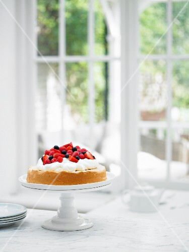 Sponge cake with cream and berries on a cake stand in the windos