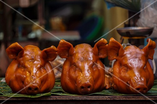 Roasted pig's heads at a market in Thailand