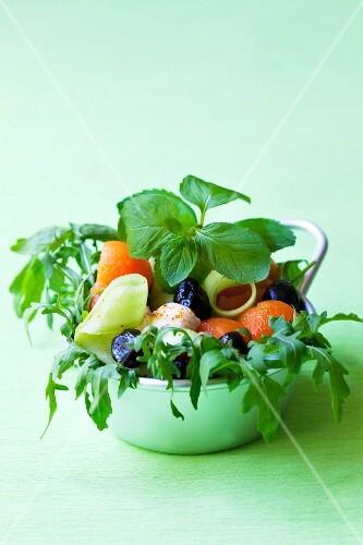 Salad with rocket, melon balls, cucumber, olives and mozzarella