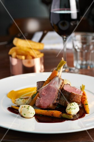 Roast lamb with carrots, chips, a glass of red wine
