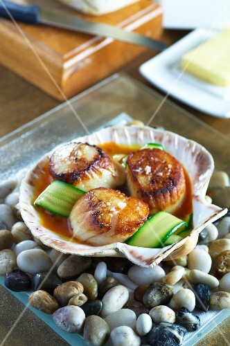 Fried scallops with courgette strips in a clamshell