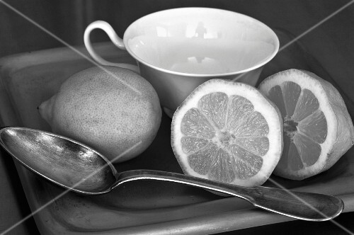 Lemons and a spoon in front of a teacup (black and white image)