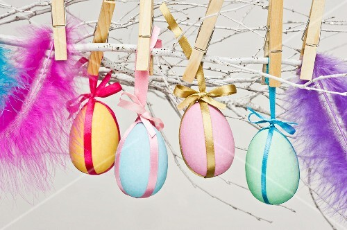 Eggs painted in bright colours for Easter, attached to twigs with clothes pegs