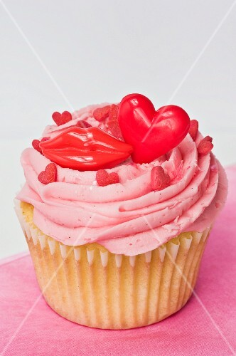 A cupcake topped with pink buttercream icing, red lips and hearts