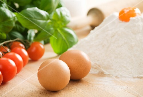 Eggs, flour, cherry tomatoes, basil and a rolling pin