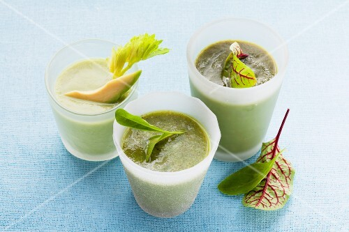 Three green smoothies in juice glasses