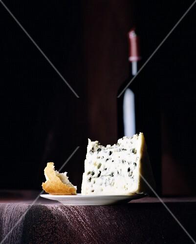 A still life featuring blue cheese, bread and a bottle of red wine