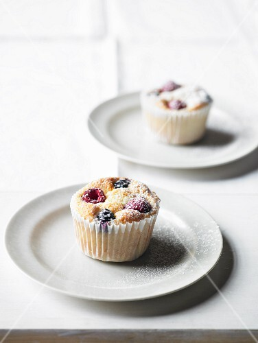 Blueberry and raspberry muffins with icing sugar
