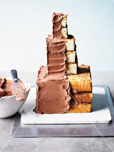 A cake in the shape of a knight's castle being spread with chocolate buttercream