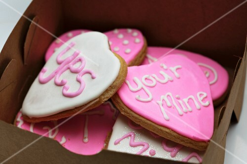 Small gingerbread hearts decorated with white and pink glacé icing