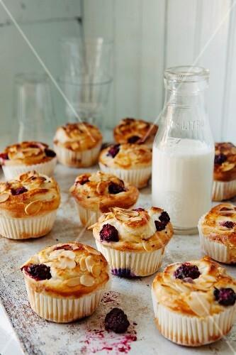Blackberry muffins with slivered almonds around a bottle of milk