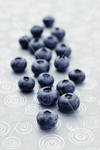 Fresh blueberries lying on a patterned tablecloth (close-up)