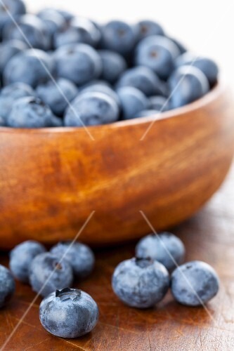 Blueberries in and in front of a wooden bowl