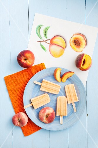 Peach and yoghurt ice lollies and fresh peaches with a drawing of peaches