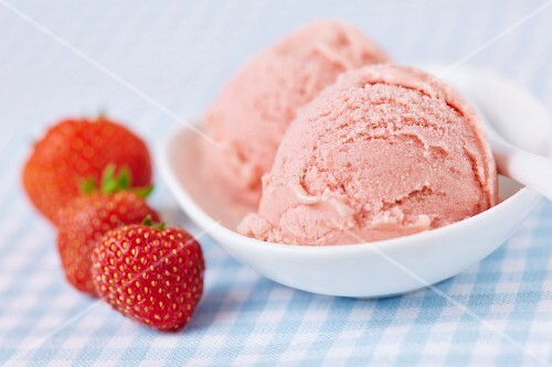 A few fresh strawberries alongside two scoops of home-made strawberry ice cream