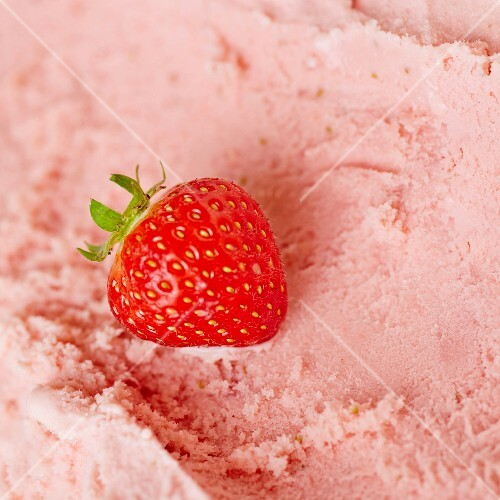 A fresh strawberry on fresh strawberry ice cream ready to be scooped